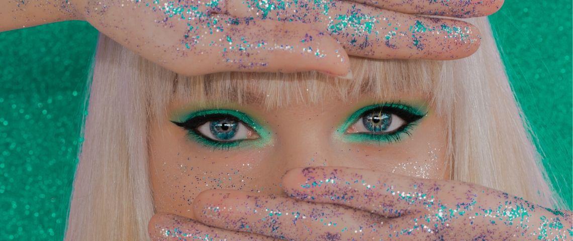 Une femme blonde avec du maquillage vert sur les yeux