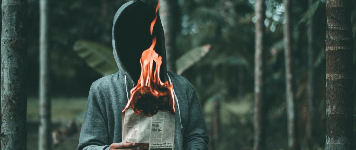 un homme à capuche dans une forêt tient un journal en feu