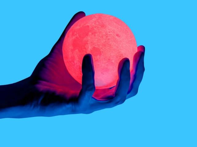 Une main sur fond bleu en train de tenir une boule lumineuse