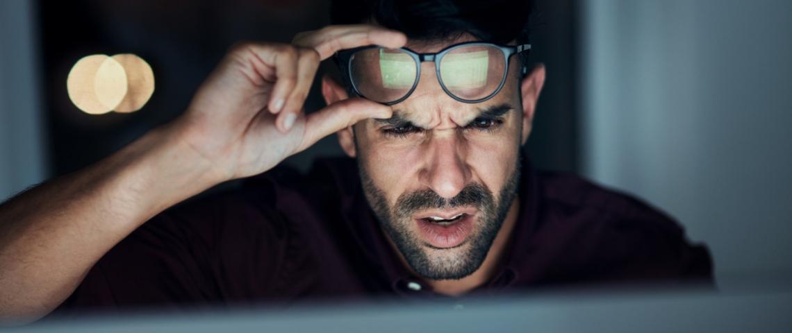 un homme fronce les sourcils et lève ses lunettes en regardant un écran.