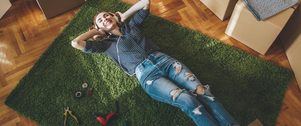Une jeune femme allongée sur de la moquette imitant de l'herbe