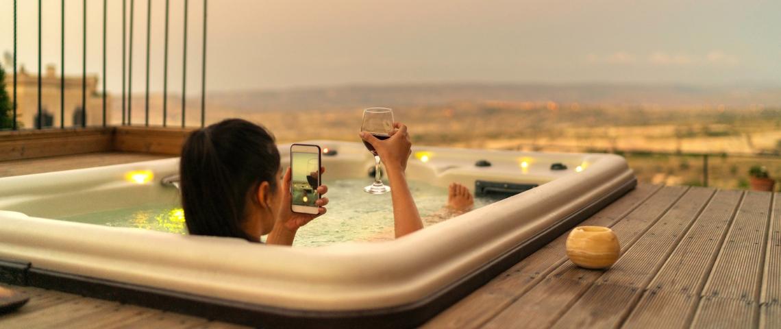 une influenceuse dans un bain qui prend en photo son verre de vin