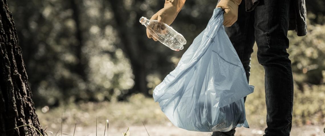 Un homme en train de jeter une bouteille en plastique dans un sac poubelle
