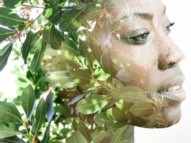 Une femme noire dont le visage est mélangé à des plantes