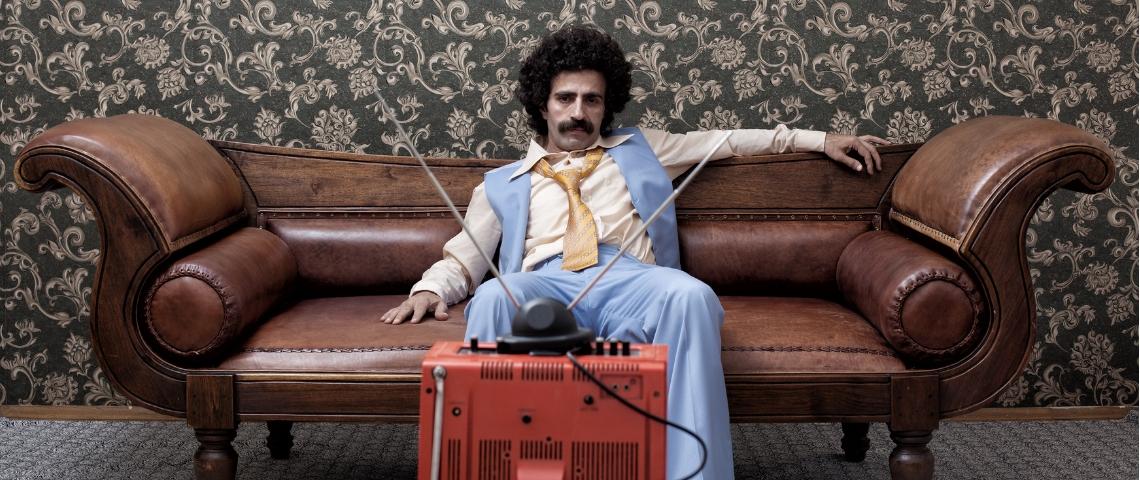 un homme moustachu regarde une télévision