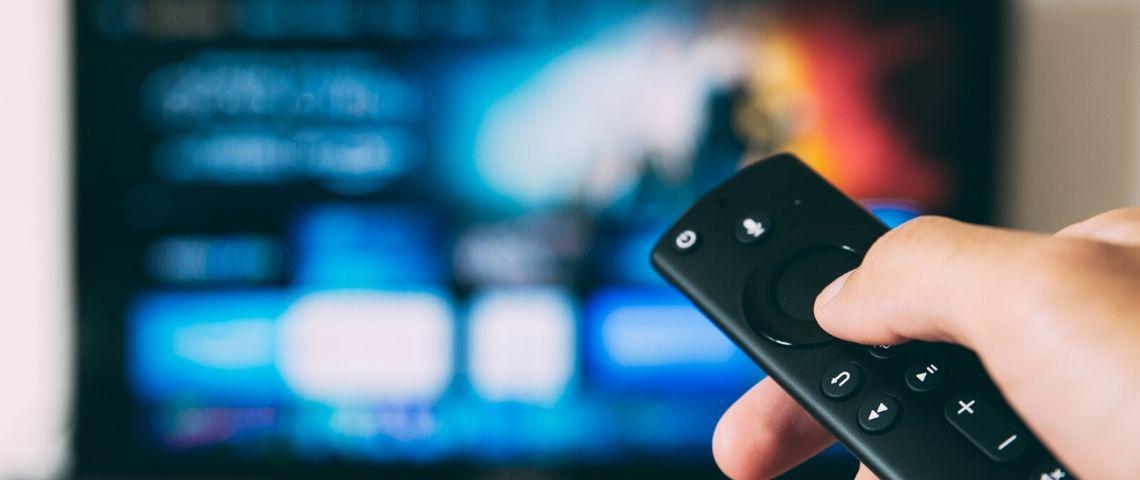 Personne tenant une télécommande dans sa main devant un écran