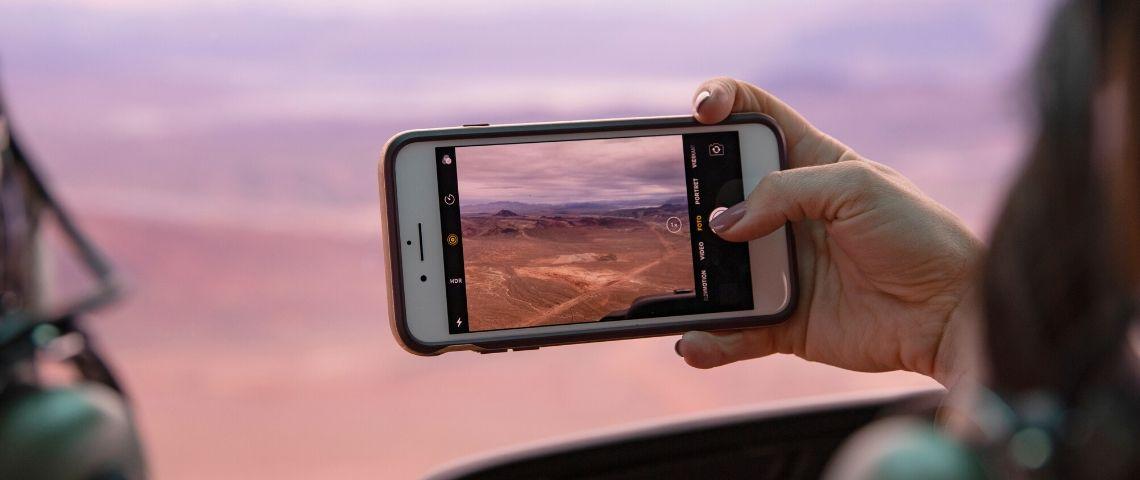 une femme prend une photo d'un paysage rose