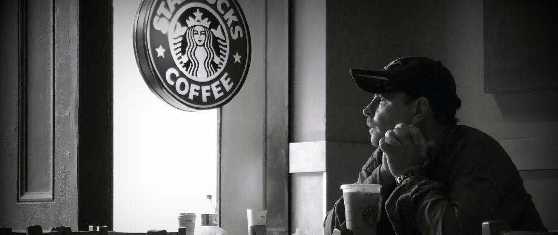 Homme buvant un café chez Strabuks