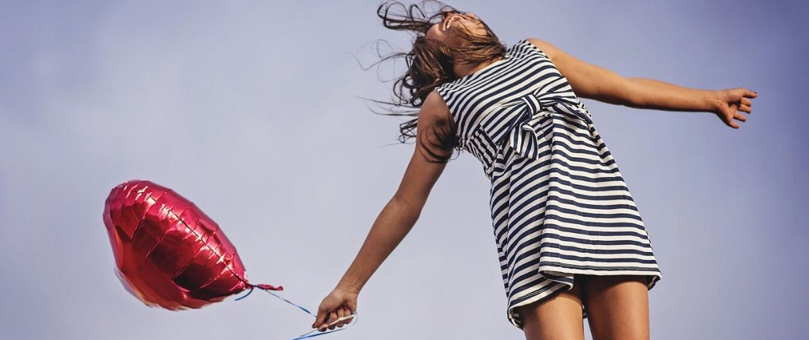 Jeune fille sautant en l'air avec un ballon rouge en forme de coeur dans la main droite