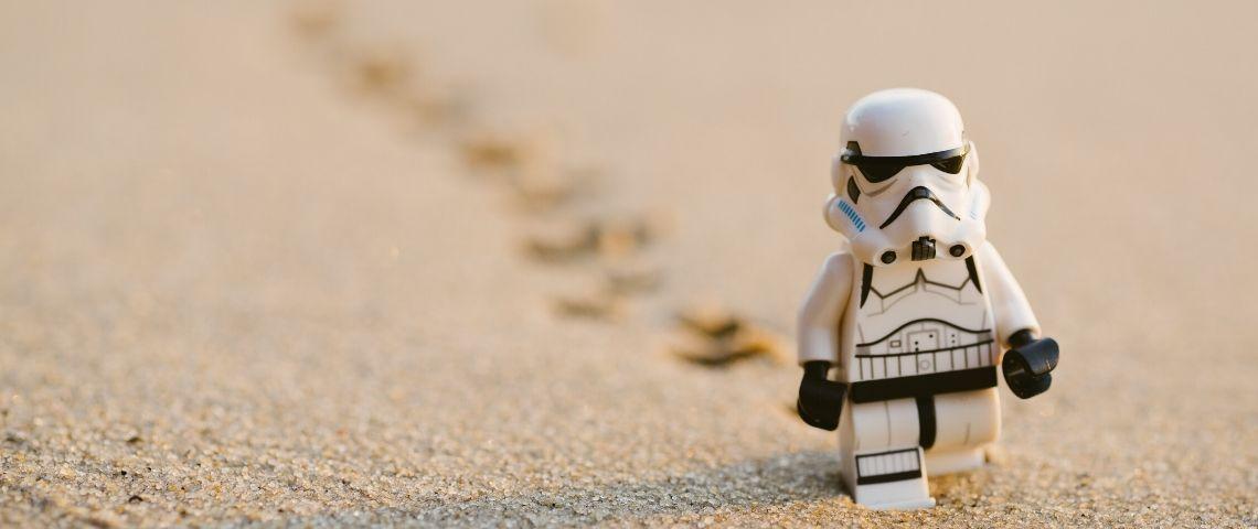 Un lego en forme de stormtrooper marche sur le sable