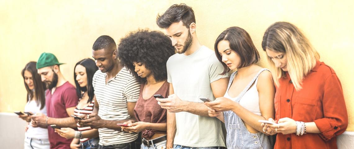une groupe de jeune gens qui regardent leur portable.