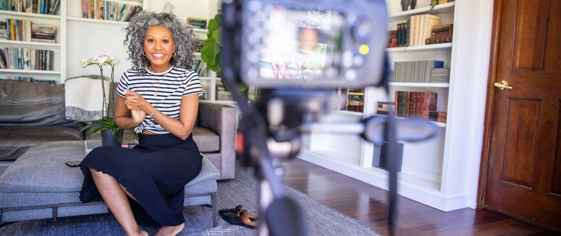 Une femme métisse souriante devant une caméra, influence