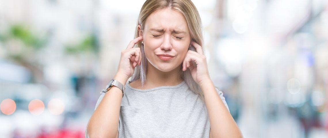 Une femme qui se bouche les oreilles