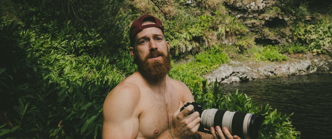 Un homme torse nu tient un appareil photo