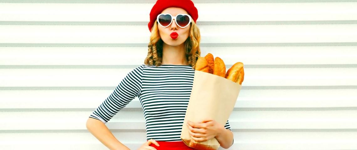 Une femme avec une marinière, un béret et des baguettes de pain