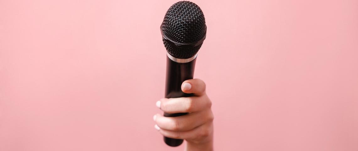 Une main de femme tendant un micro