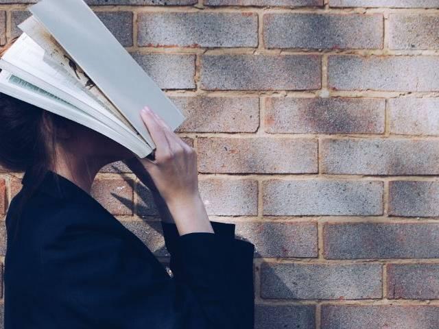 Une femme avec un cahier sur la tête