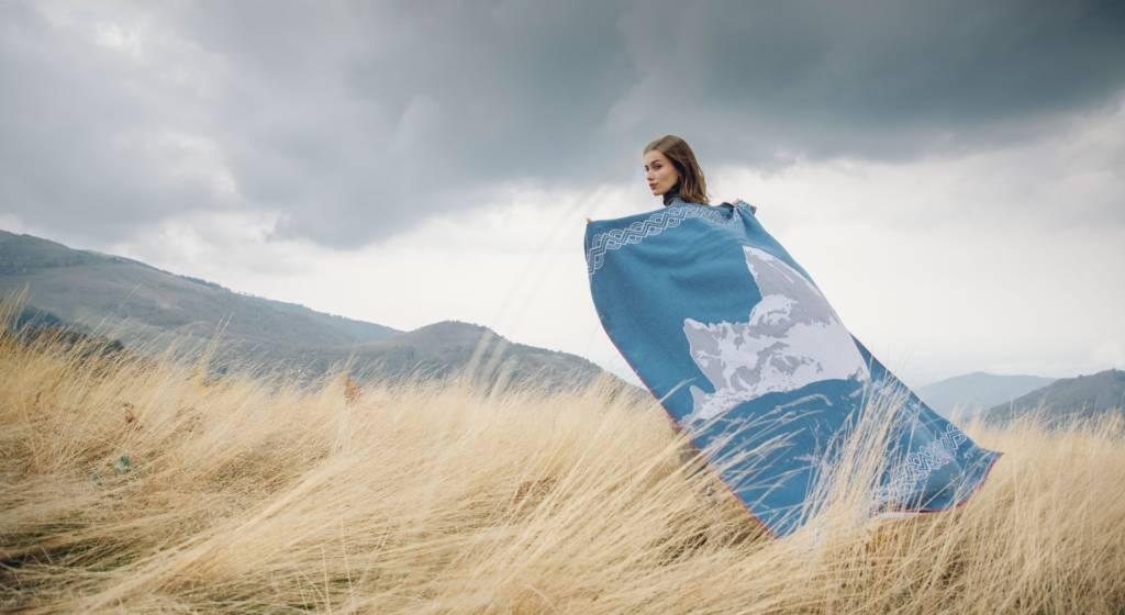 Jeune femme dans un champ de céréale laissant flotter un foulard derrière elle