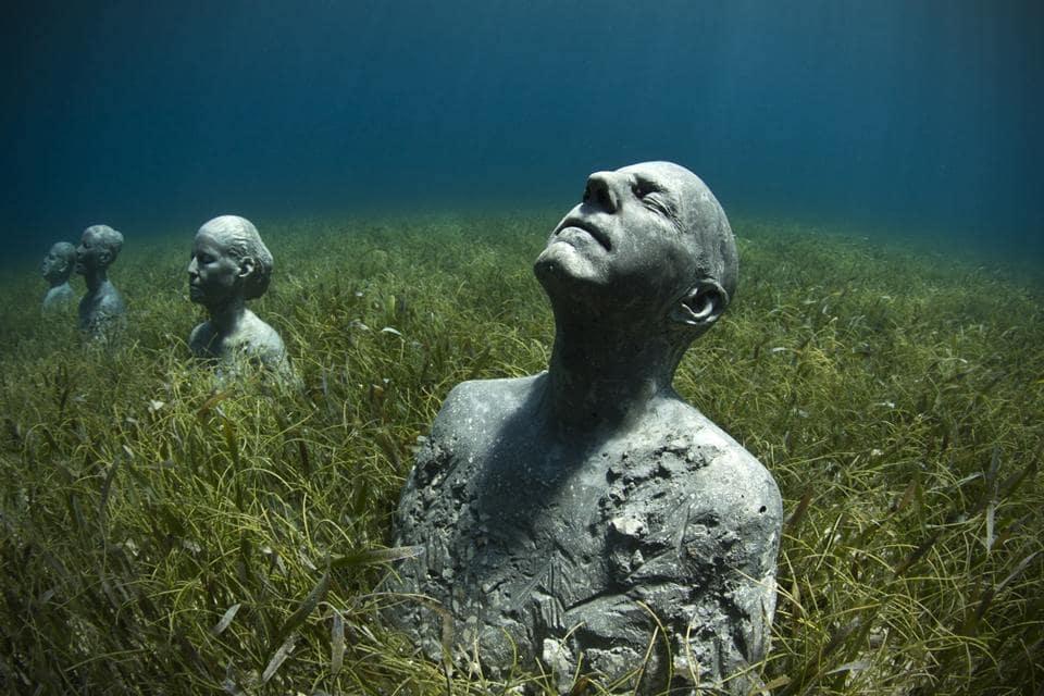 des sculptures de visages immergées dans l'eau