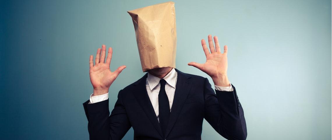un homme avec un sac en papier sur la tête qui lève les mains