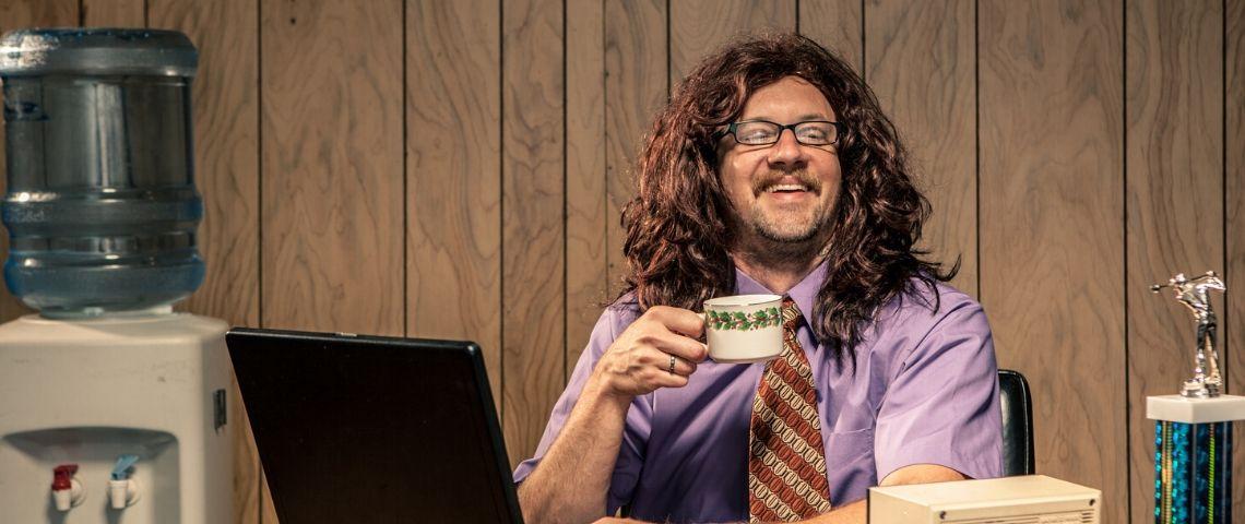 un homme assis à une bureau dans une chemise violette