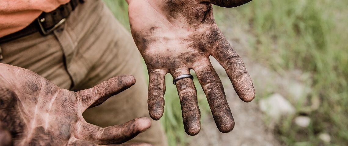 Mains d'agriculteur pleine de terre