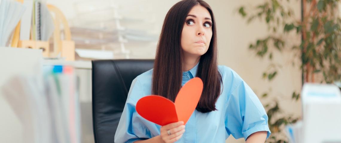 Une femme dans un bureau en train de tenir un coeur rouge en papier