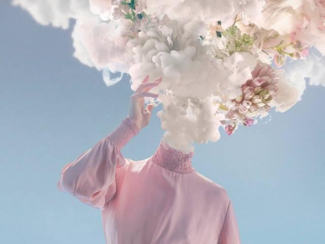 Une femme dont la tête est remplacée par un nuage et des fleurs