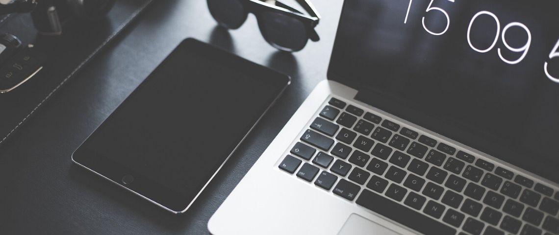 Ordinateur et tablette sur une table avec une paire de lunette noires sur le côté
