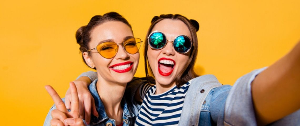deux filles dont un selfie devant un mur jaune