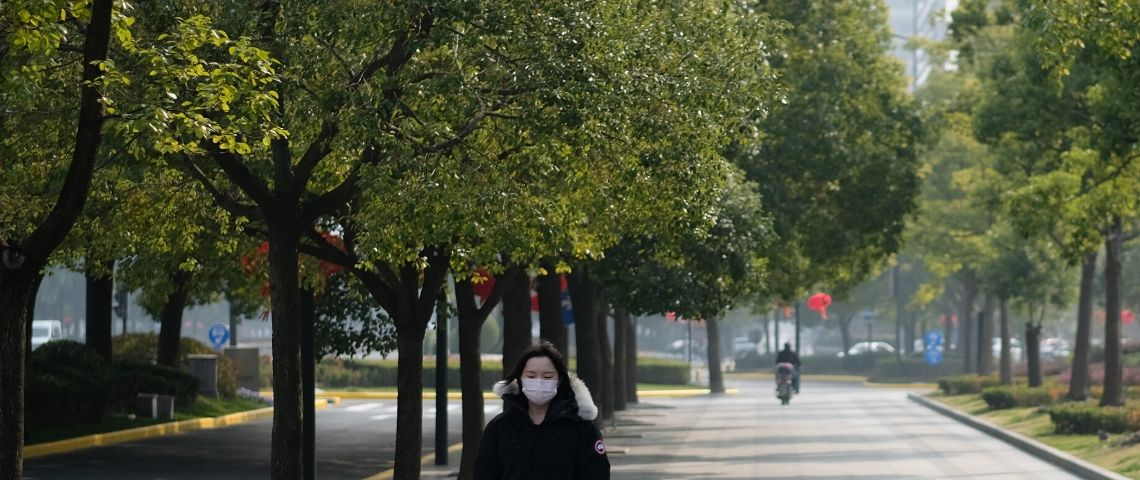 Une femme en Chine avec un masque sur le visage et des arbres autour