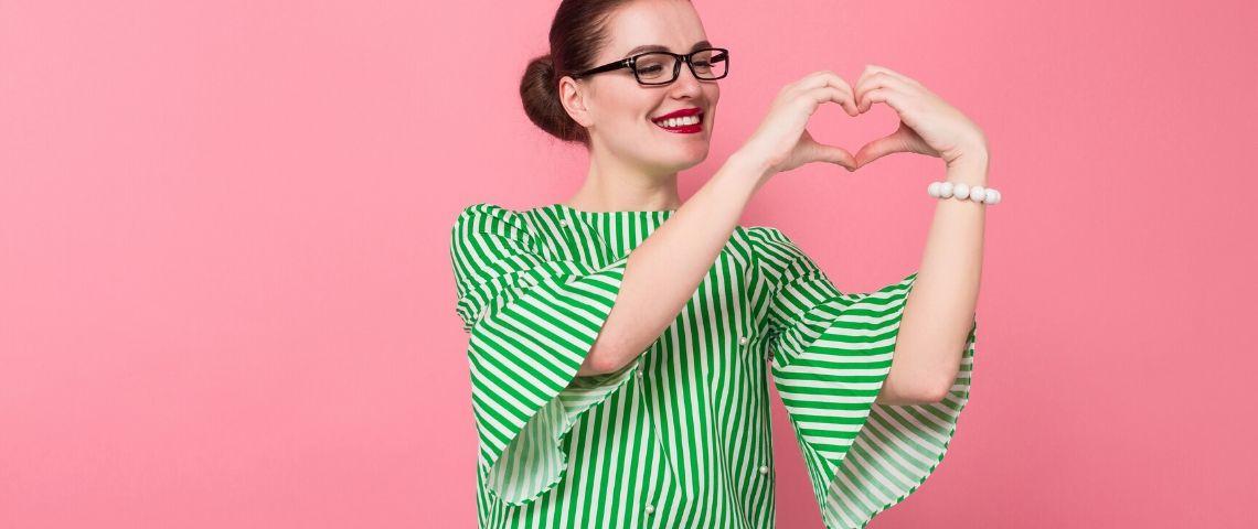 Une femme fait un coeur avec ses doigts