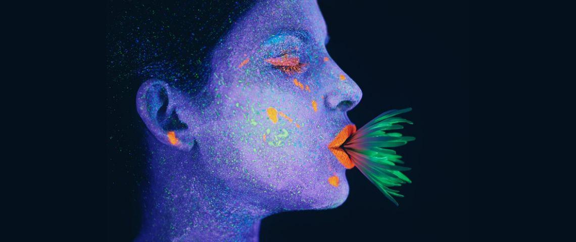Une femme au visage bleu avec une plante verte dans la bouche