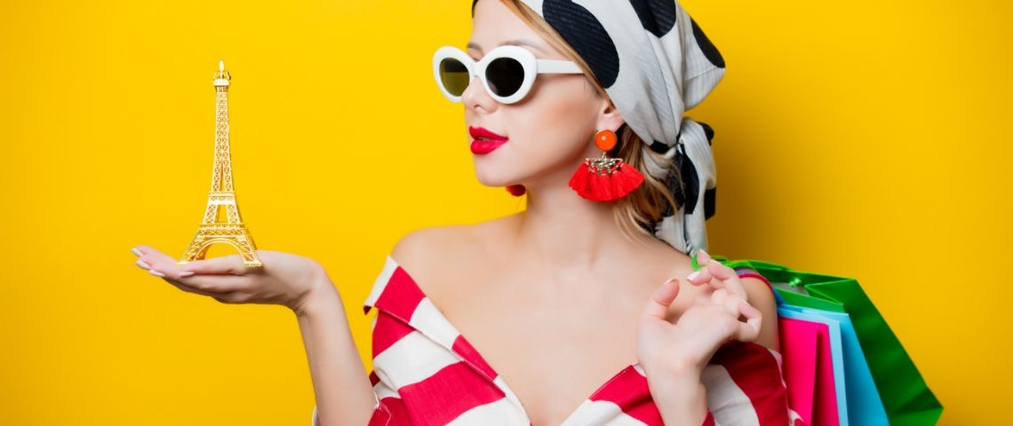 Une femme avec un foulard et des lunettes qui tient un Tour Eiffel dans sa main