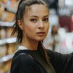 Une femme en train de choisir des produits dans les rayons d'un supermarché