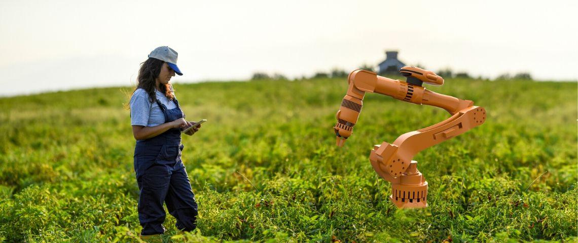 une femme en salopette dans un champ une tablette à la main face à un robot orange