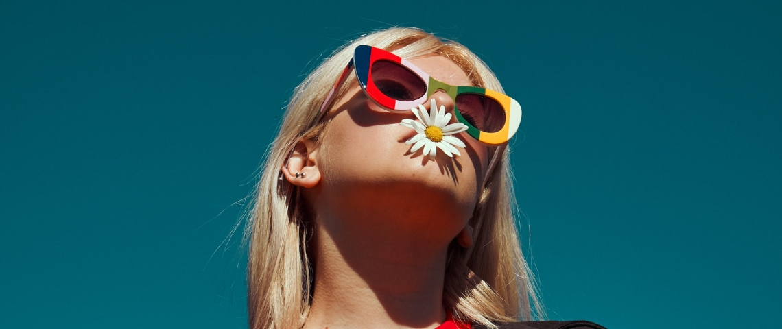 une jeune fille qui à une fleur dans la bouche