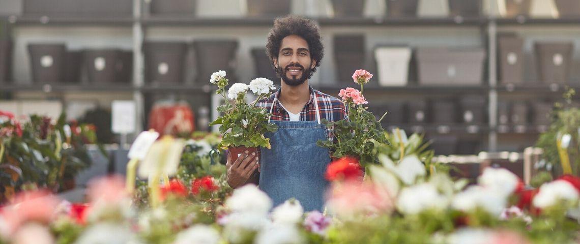 Fleuriste avec des pots dans les mains souriant