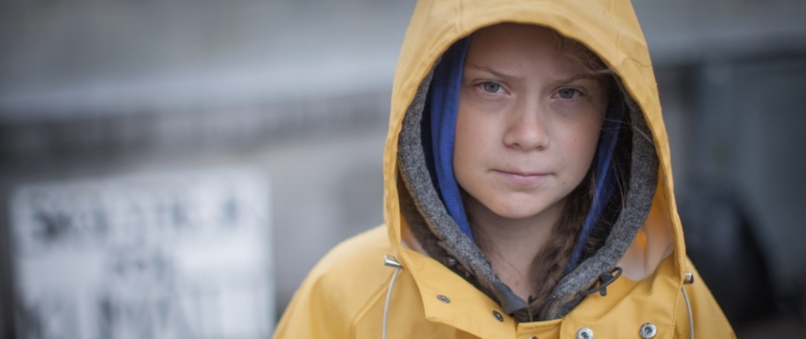 une jeune fille en imperméable jaune qui fixe la caméra
