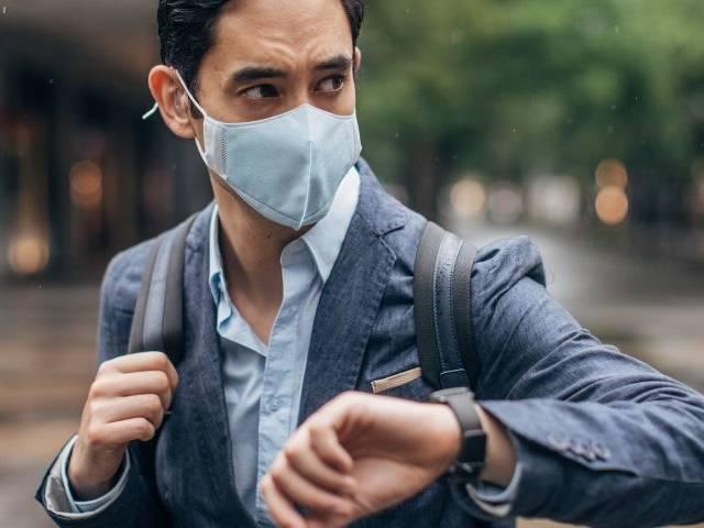 un homme en costume porte un masque