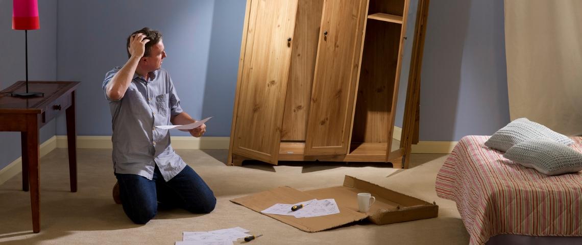 Un homme en train de monter une armoire bancale