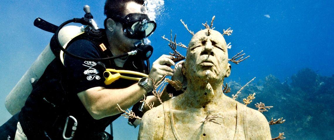 un plongeur sculpte sous l'eau