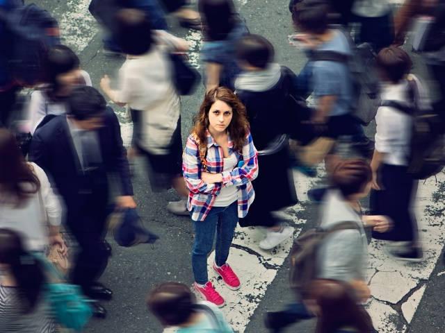 Une jeune fille entouré par la foule regarde une caméra