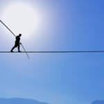 Un homme en train de marcher sur une corde entre deux falaises