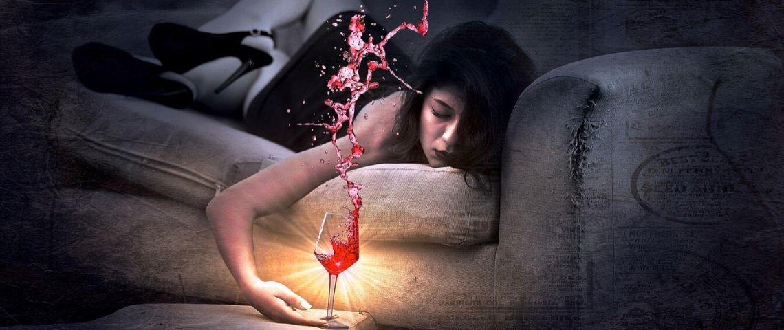 Femme allongé sur un canapé, s'endormant, un verre à la main