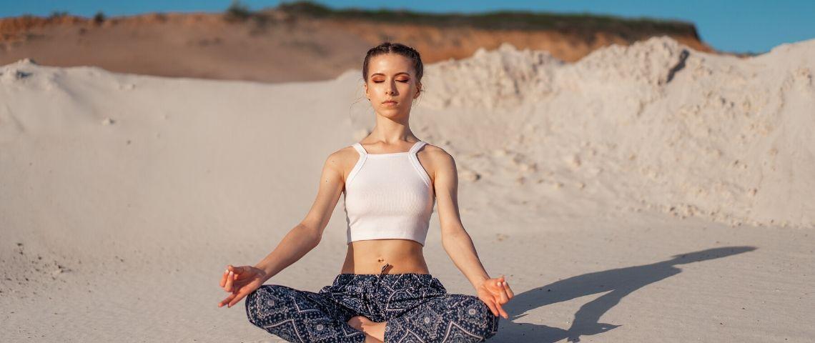 Une femme qui fait du yoga sur la plage