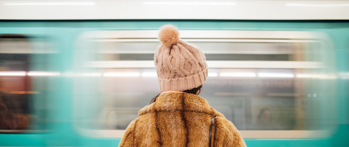 une fille en manteau de fourrure de dos face à un métro