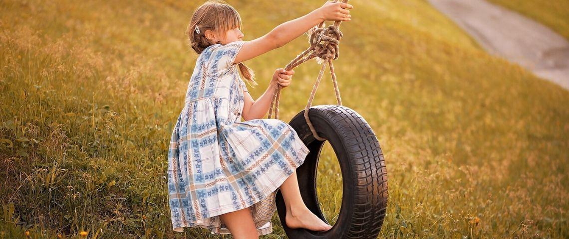 Petite filel faisant de la balancoire sur un pneu