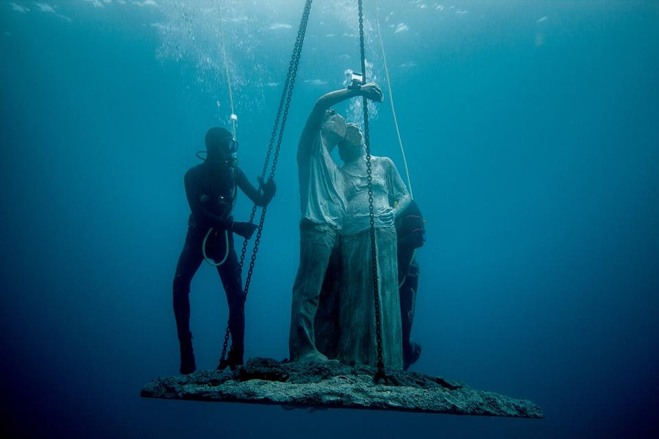 un plongeur immerge une sculpture sous l'eau