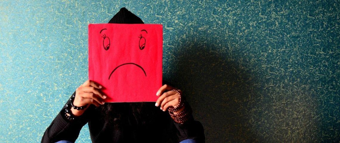 Personne assise par terre, en noir, tenant devant son visage une feuille A4 rouge avec les traits d'un visage triste